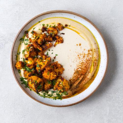 Roasted Harissa Cauliflower on Hummus with Tahini Sauce